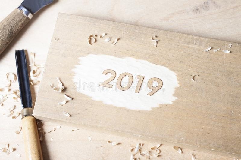 Carved wooden digits 2019 of the New Year on old rustic wooden table. Carved wooden digits forming number 2019 of the New Year on old rustic wooden table stock image