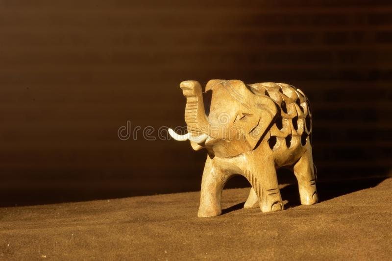 Carved wooden figure of an elephant with a trunk raised to the top. NToy elephant on dark background stock images