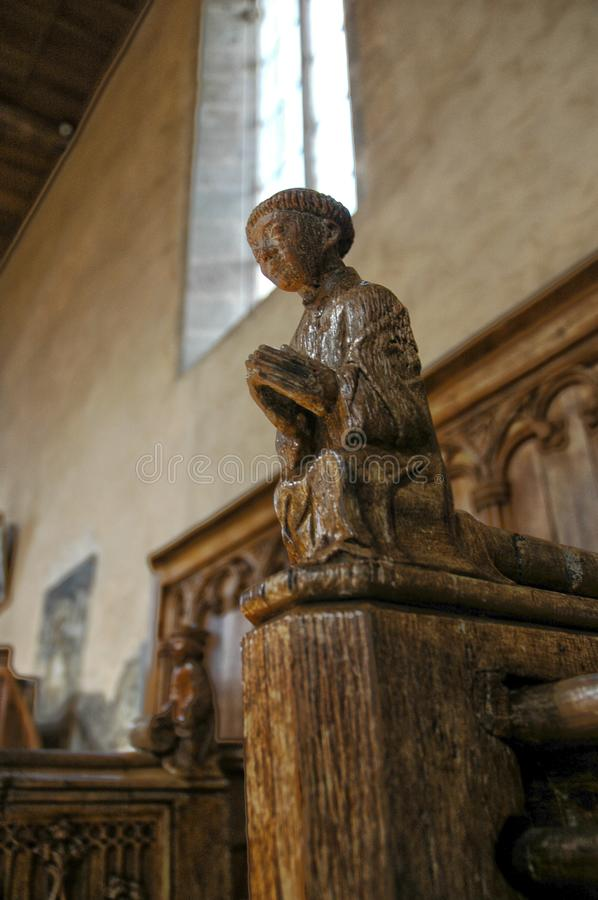 Carved wooden figure praying in chapel royalty free stock photo