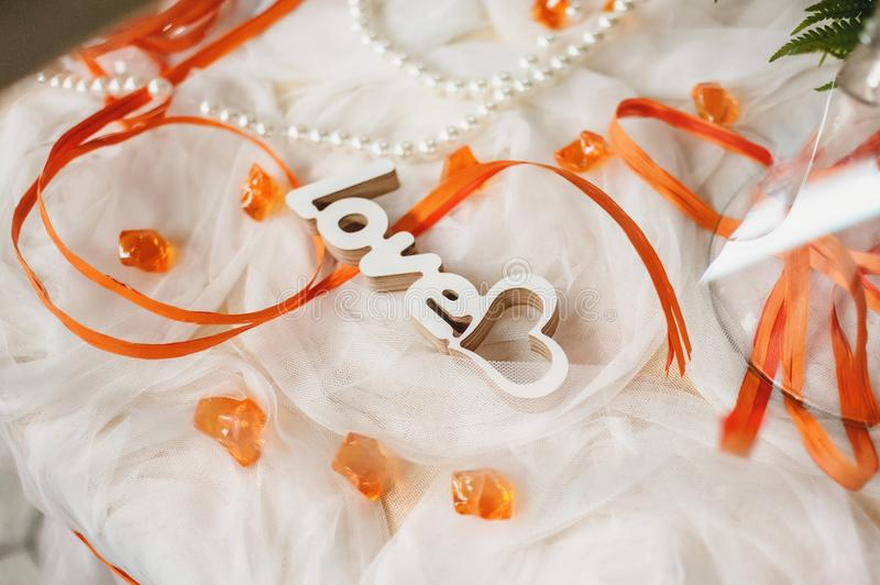 Carved wooden word love is in tulle with orange ribbons stock images
