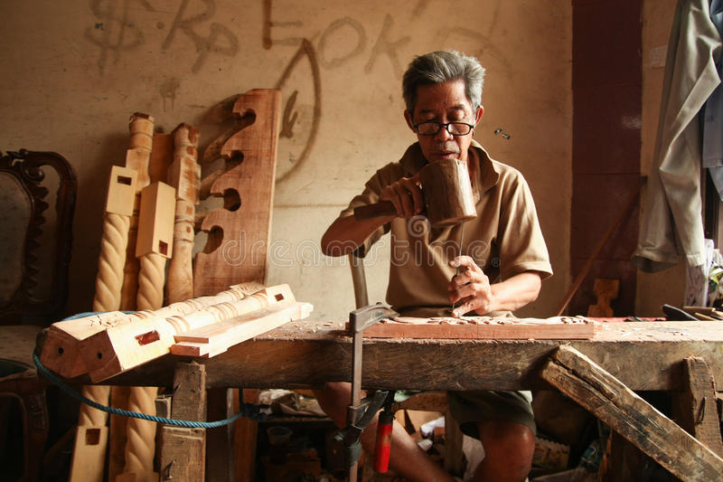 The Carver. A carver is finishing a gamelan Gong Home Factory, Bogor, West Java, Indonesia stock images