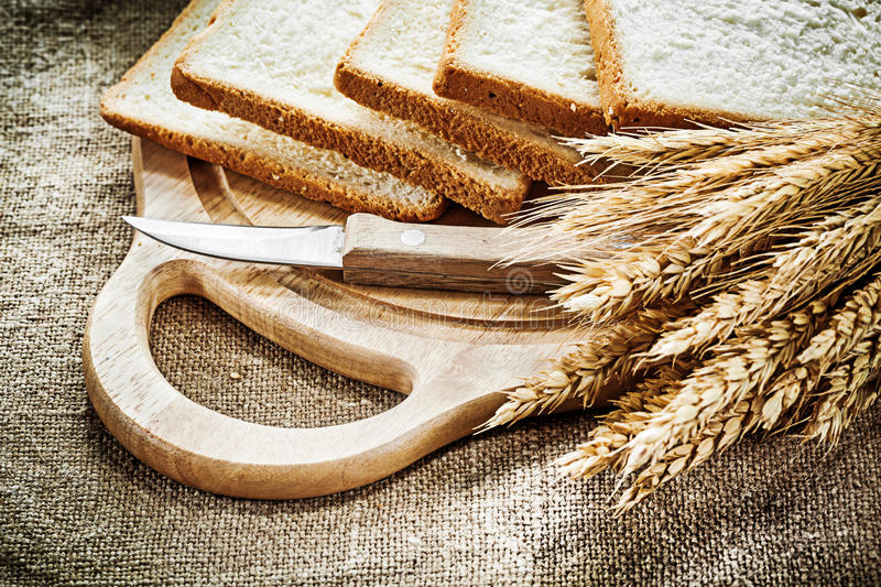 Carving board kitchen knife sliced bread rye ears on hessian bac. Kground stock photos