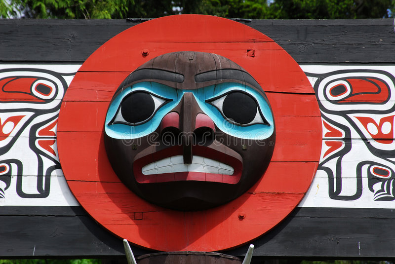 Carving face on a totem pole royalty free stock photo