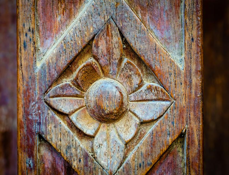 Carving of a flower design on wood. Traditional wood carving of a flower on an old battered wooden panel royalty free stock photo