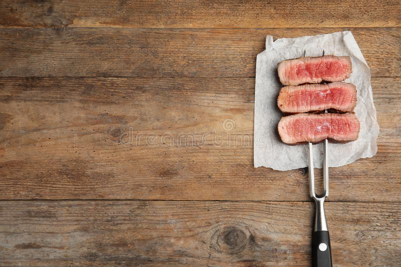Carving fork with slices of delicious beef steak on table, top view. Space for text royalty free stock images