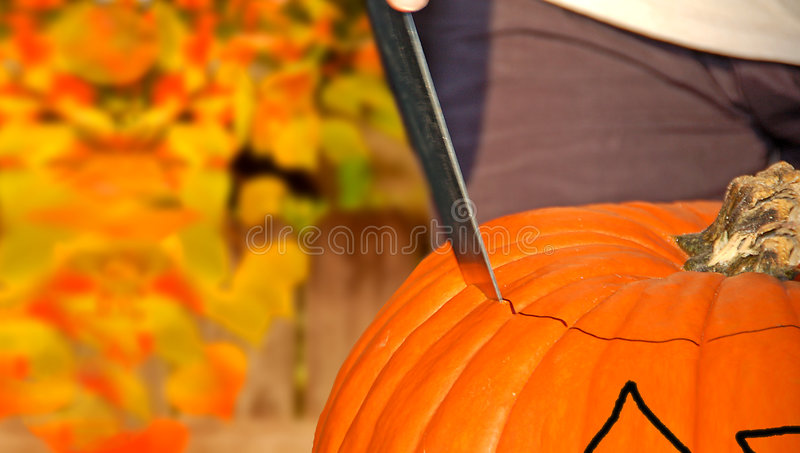 Carving Halloween Pumpkin. Carving the lid on a halloween pumpkin or jackolantern in autumn setting stock images