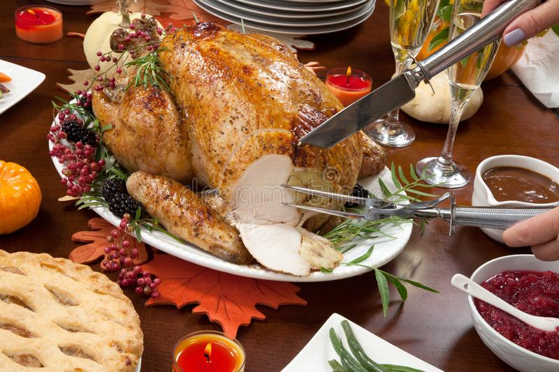 Carving Pepper Turkey for Thanksgiving. Carving roasted pepper turkey for Thanksgiving, garnished with pink pepper, blackberry, and fresh rosemary twigs on a royalty free stock photos