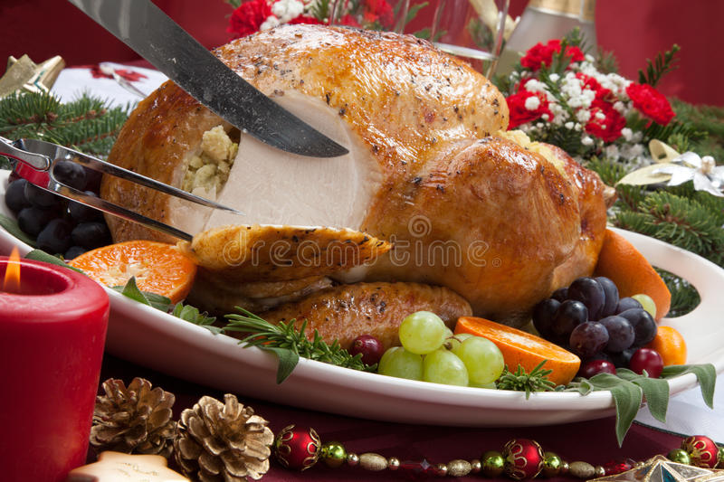 Carving Roasted Turkey for Christmas Dinner. Carving roasted herb rubbed turkey garnished with fresh grapes, oranges, and cranberry is ready for Christmas dinner royalty free stock image