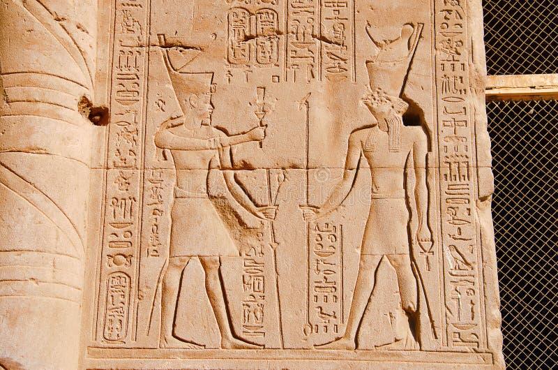 Carvings på den inre väggen av den Edfu templet, är det en av de bästa bevarade relikskrina i Egypten, hängivet till falkguden Ho arkivbilder