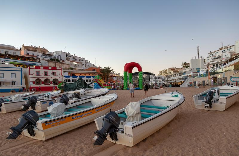 Early evening view of cave tour boats on the beach with Carvoeiro town square behind. stock photography