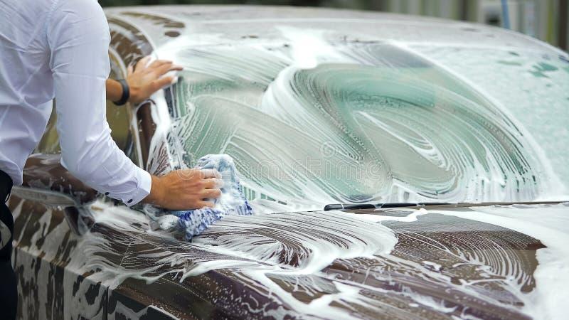 Carwash costoso, coche masculino ocupado de la élite que se lava con la espuma de la limpieza, negocio fotografía de archivo libre de regalías