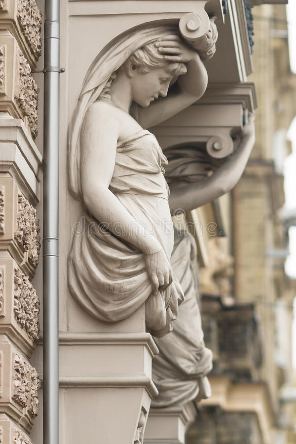 Caryatid on one of the buildings in Riga, Latvia. Statue of female caryatids in the center of Riga, Latvia on a rainy autumn day stock photo