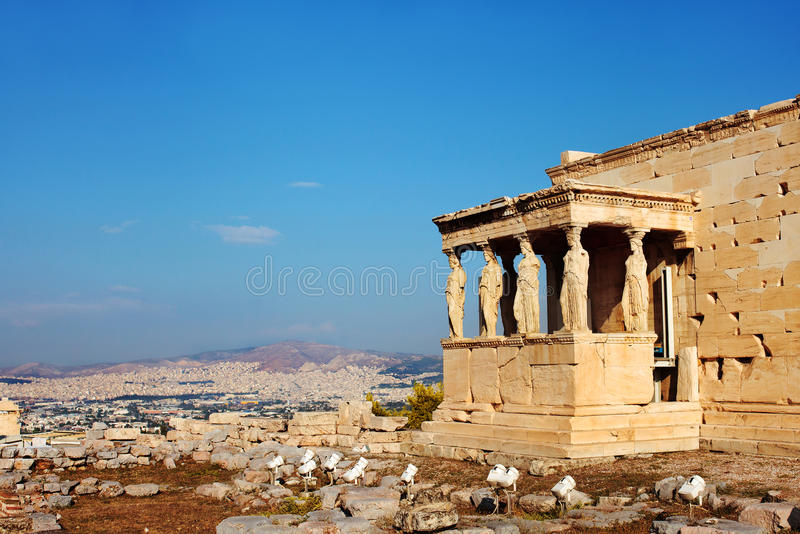 Caryatids columns and temple. Athens, Greece. Focus on the Caryatids columns with Athens in the background. Part of the Erechtheion temple in the Acropolis stock image