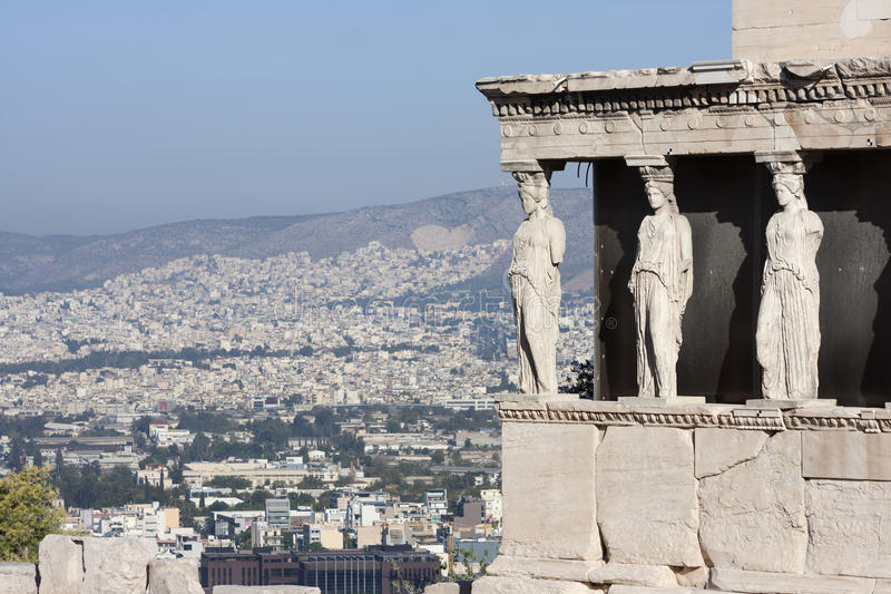 Caryatids in Erechtheion temple. The caryatids in the Erechtheion of Erechtheum, the ancient greek temple in the Acropolis of Athens with a view of the cityscape stock image