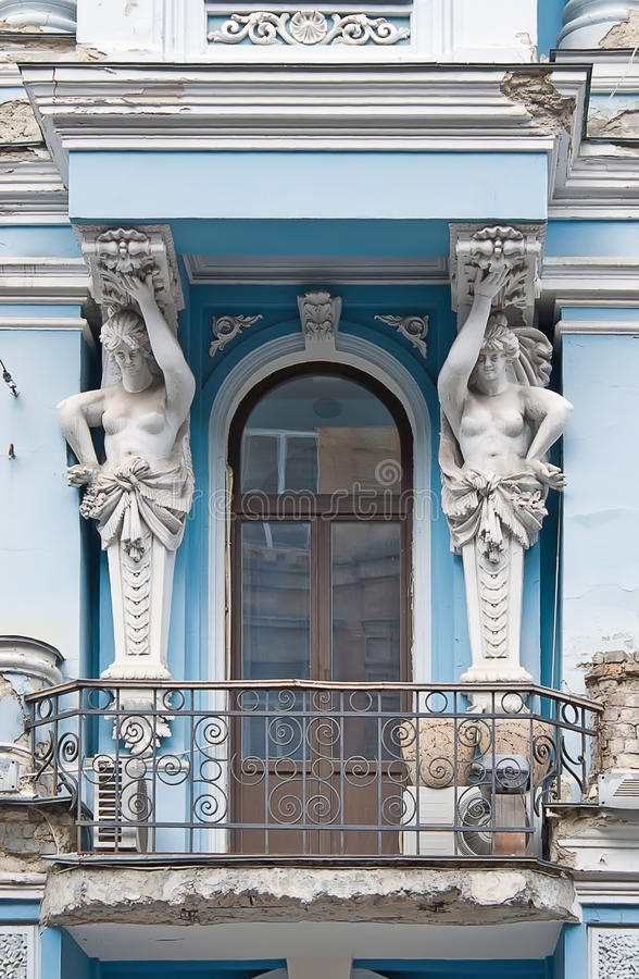 Caryatids supporting the balcony. Of the ancient house royalty free stock image