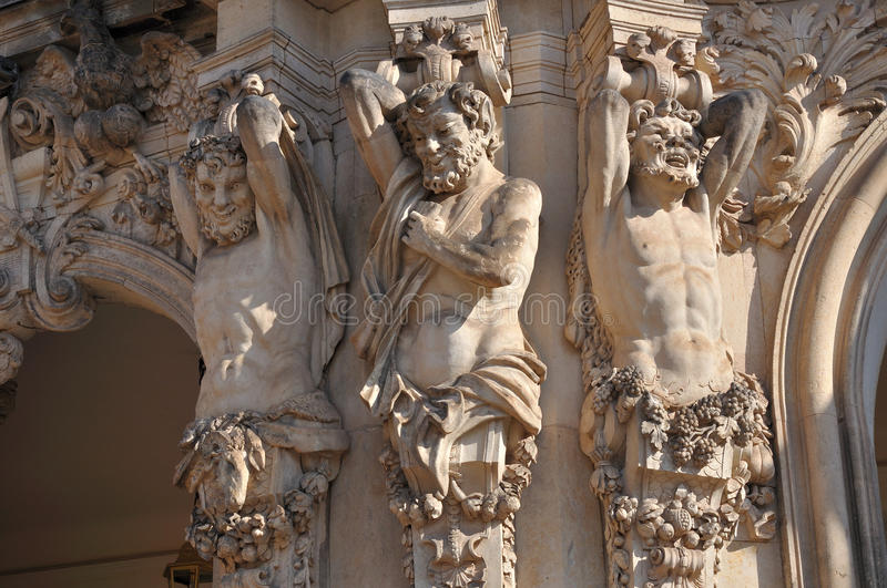 Caryatids at zwinger, dresden. Grotesque sandstone statues that act as caryatids on a portal at a famous palace and museum in dresden, the building has been royalty free stock image