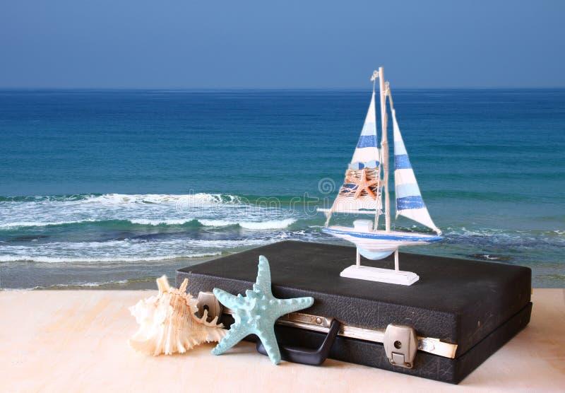 Cas de vintage avec le vieux jouet de bateau et étoiles de mer devant le paysage marin concept de course photographie stock libre de droits