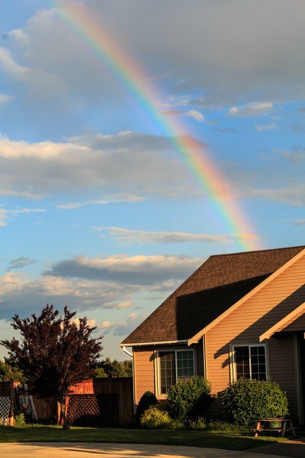 A casa é o potenciômetro de ouro na extremidade do arco-íris fotografia de stock royalty free