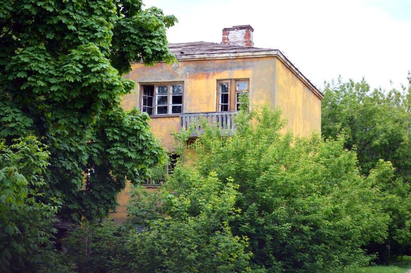 Casa abandonada com uma tubula??o do tijolo em arvoredos verdes densos foto de stock