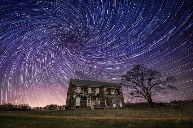 A casa abandonada da exploração agrícola com estrela espiral arrasta no céu fotos de stock