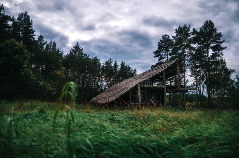 Casa abandonada de madera fantasmagórica en bosque espeluznante en el crepúsculo fotografía de archivo libre de regalías