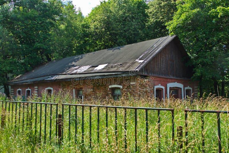 Casa abandonada do tijolo vermelho cercada por árvores e por grama imagem de stock