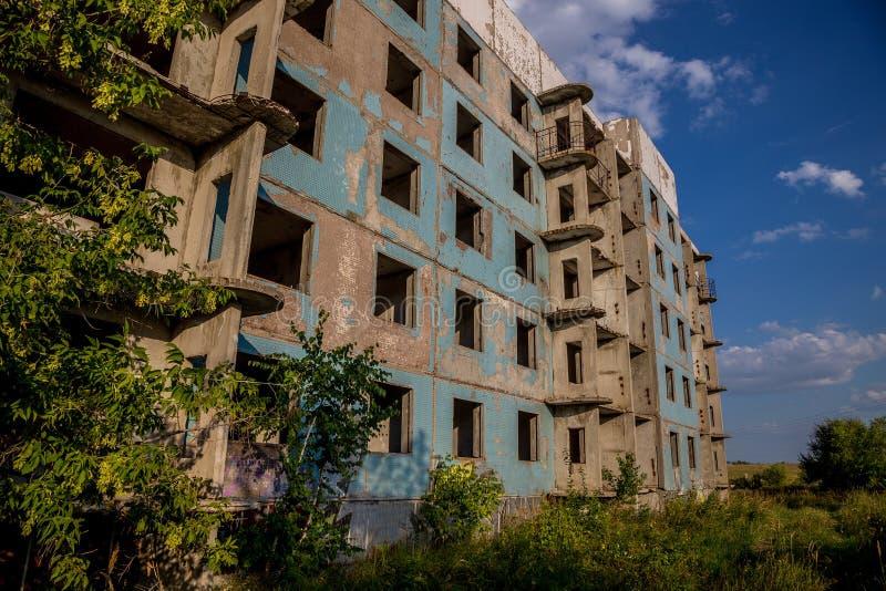 Casa abandonada e coberto de vegetação da cinco-história na cidade fantasma, verão imagens de stock