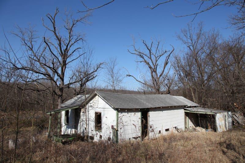 Casa abandonada en medio de malas hierbas y de árboles fotografía de archivo libre de regalías