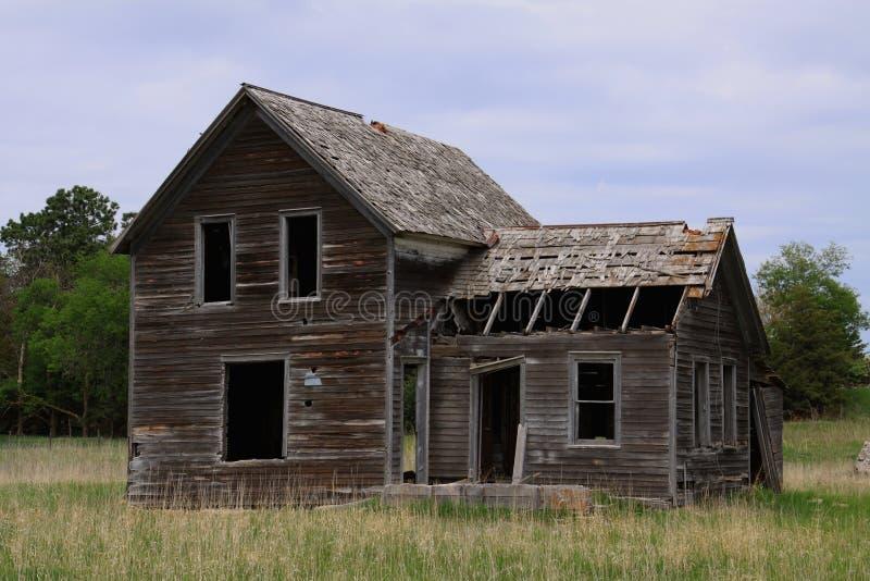 Casa abandonada rural da exploração agrícola cercada pela grama de pradaria fotografia de stock royalty free