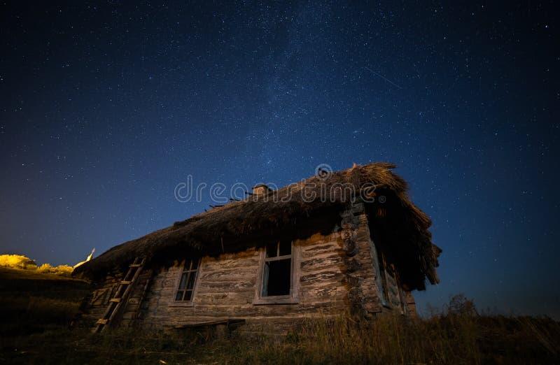 Casa abandonada ucraniano en el pueblo viejo Contra la perspectiva de la vía láctea fotografía de archivo