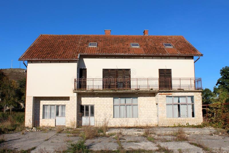 Casa abbandonata della famiglia numerosa con i ciechi di finestra di legno chiusi ed il balcone anteriore lungo circondati con le immagini stock libere da diritti