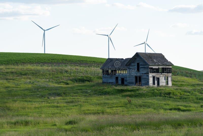 Casa abbandonata spettrale e vecchia dell'azienda agricola nella Rolling Hills del Palouse in Washington State Mulini a vento nel fotografia stock