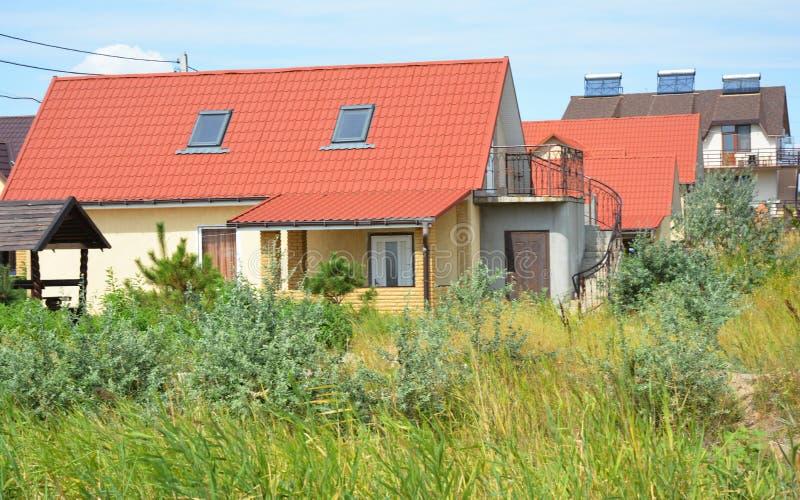 Casa acogedora de la cabaña con los shylights rojos de la ventana del tejado, del balcón y del ático del metal foto de archivo