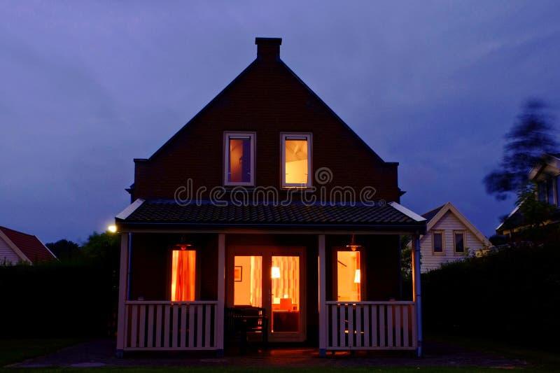 A casa acolhedor do feriado com varanda iluminou-se na noite fotografia de stock royalty free