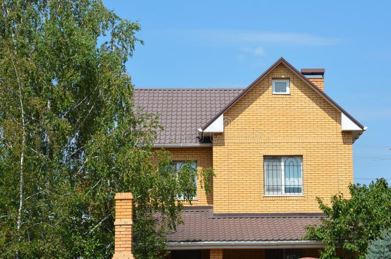Casa acolhedor do tijolo com telhado do metal, sótão, grade da janela do metl, chaminé e árvores do jardim fotografia de stock royalty free