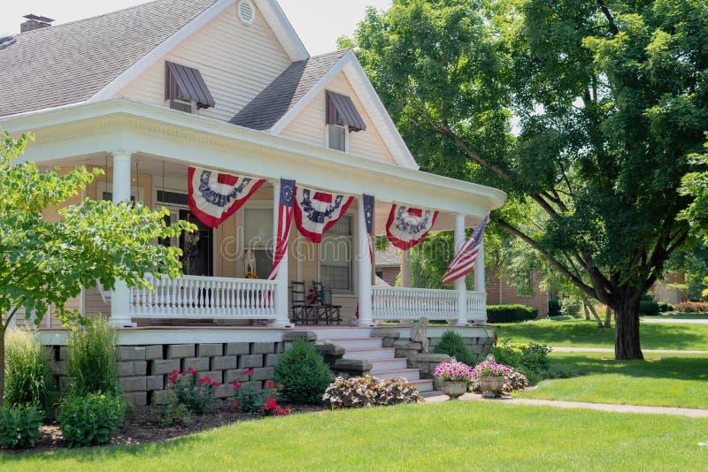 Casa affascinante decorata con le bandiere americane per il quarto di Ju immagine stock