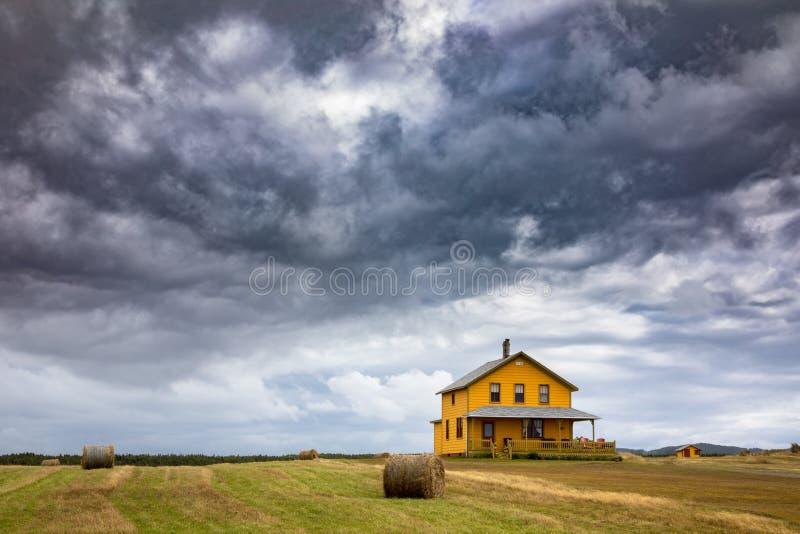 Casa amarela e céus tormentosos em Magdalen Islands imagem de stock