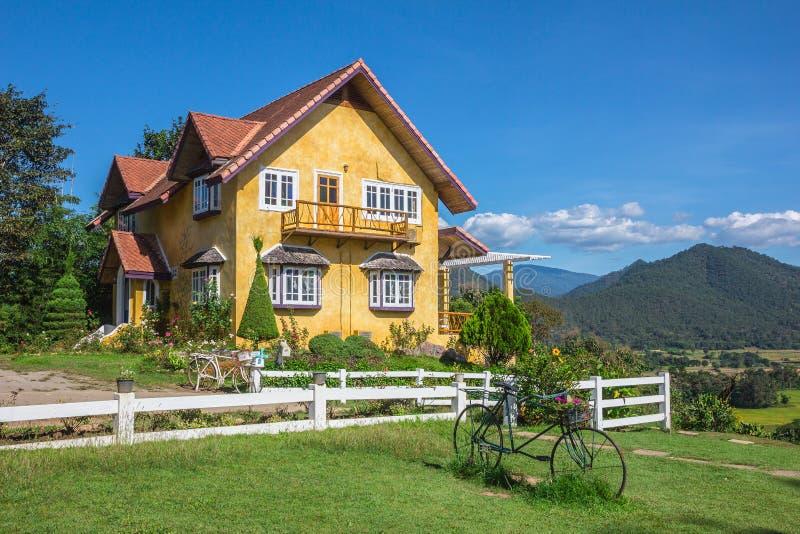 Casa amarela encantador e um fundo bonito do céu com jardim e montanha na parte traseira imagem de stock