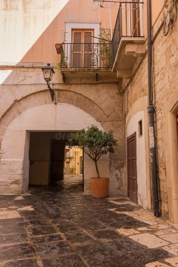 Casa amarela italiana antiga do tijolo com arco e potenciômetro e lanterna da árvore Jarda medieval com balcone e árvore fotos de stock