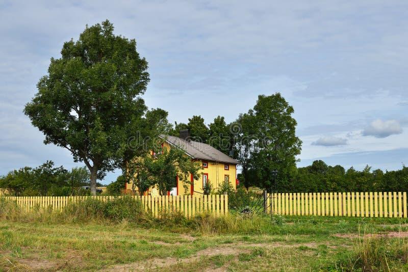 Casa amarilla acogedora al lado del campo imagen de archivo libre de regalías
