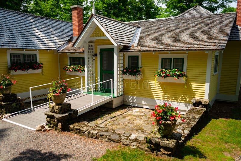 Casa amarilla de madera vieja hermosa en bosque imagenes de archivo