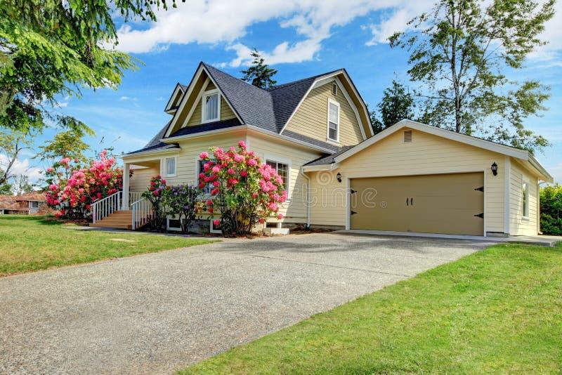 Casa amarilla exterior con rododendro floreciente de la primavera fotografía de archivo