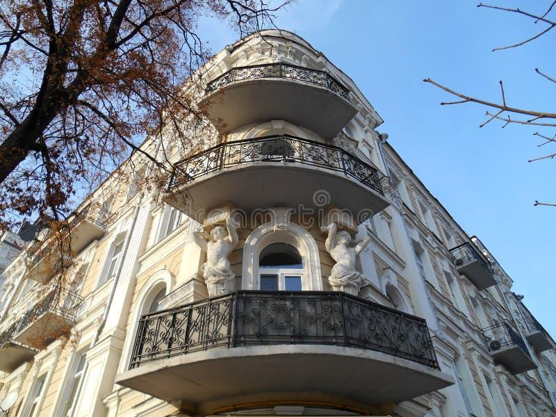 Casa antica nei colori pastelli con i bei elementi e cariatidi architettonici su un fondo di cielo blu Kyiv, Ucraina immagine stock