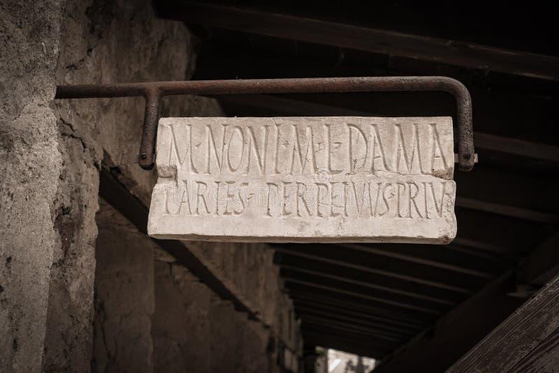 A casa antiga assina dentro a cidade histórica de Pompeia fotos de stock