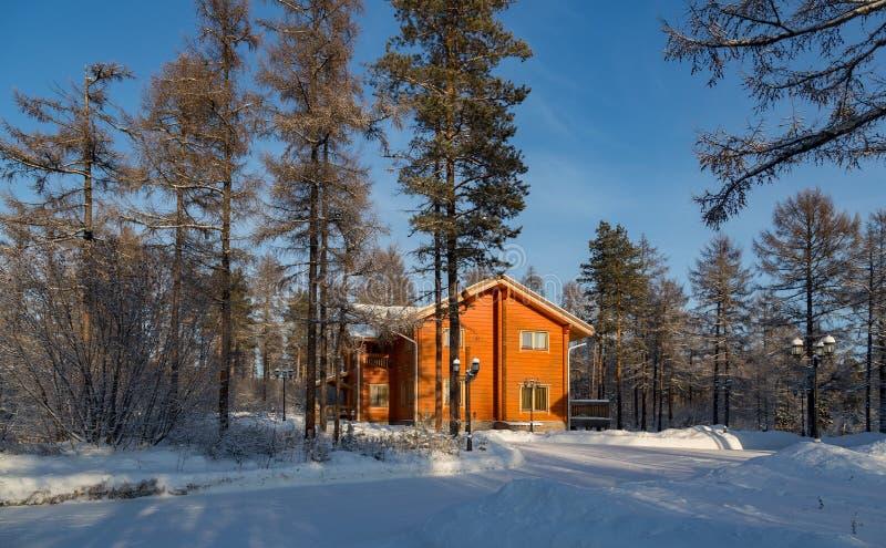 Casa arancio luminosa nella foresta di inverno fotografia stock libera da diritti