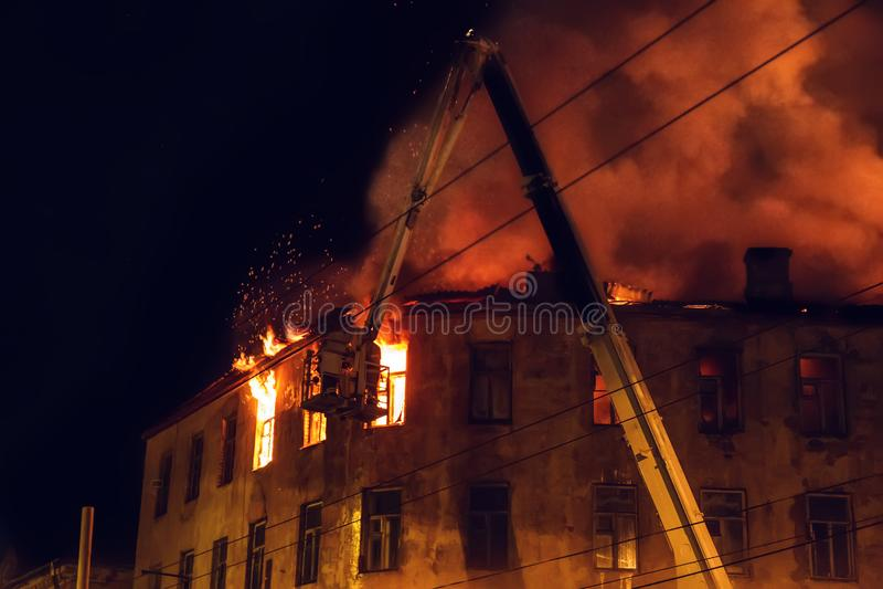 A casa ardente na noite, o telhado da construção nas chamas do fogo e o fumo, sapador-bombeiro no guindaste extinguem o fogo com  foto de stock royalty free