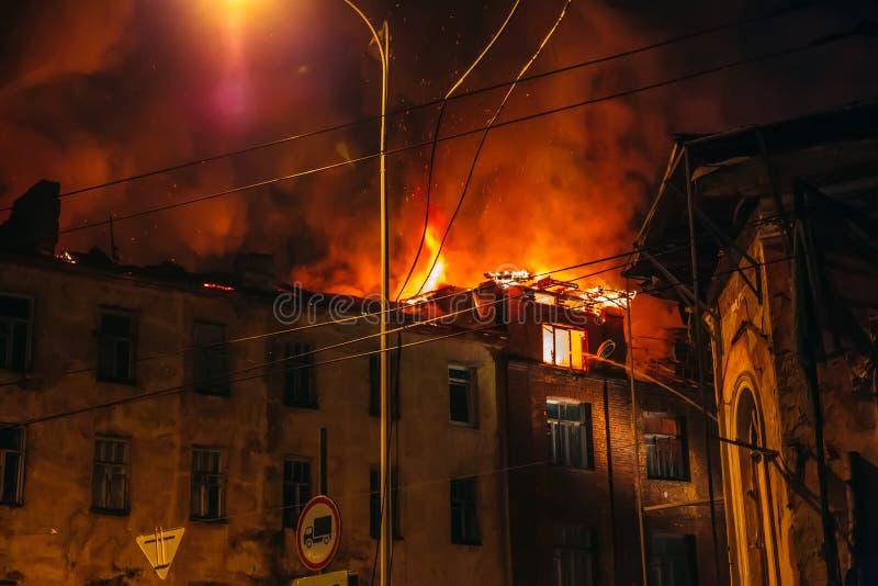 Casa ardiente en la noche, tejado del edificio en llamas del fuego y humo imagen de archivo libre de regalías