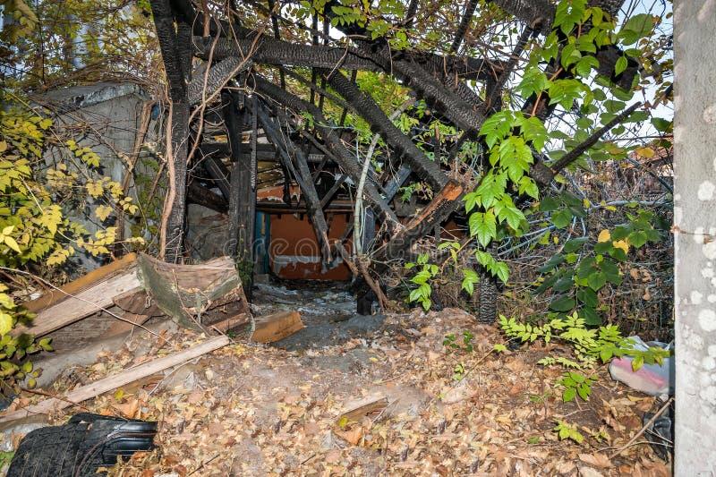 Casa arruinada y derrumbada quemada y dañada en el fuego con los restos de los polos de madera del refuerzo del foco selectivo de fotos de archivo