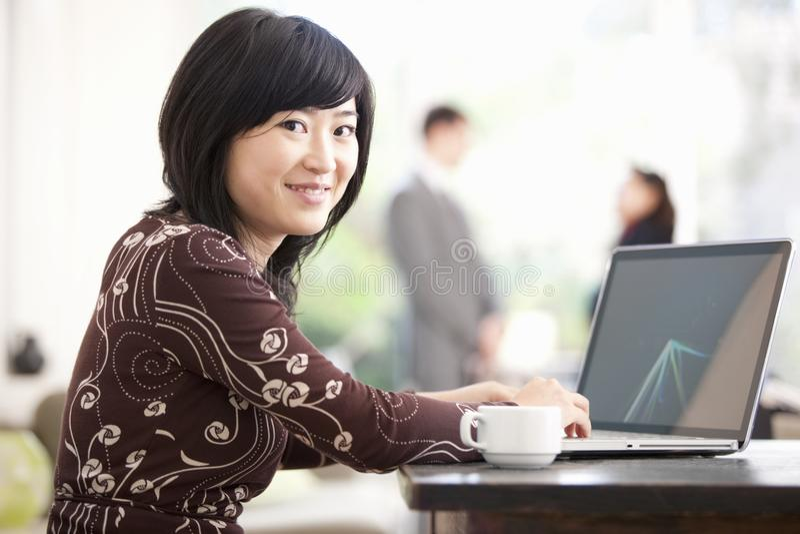 Casa asiatica di Using Laptop At della donna di affari immagini stock