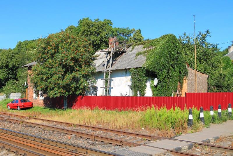 A casa atrás de uma cerca vermelha na estrada de ferro foto de stock royalty free
